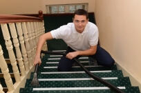 A man cleaning carpet on stairs