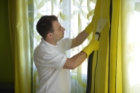 Man in white shirt and gloves cleaning curtains