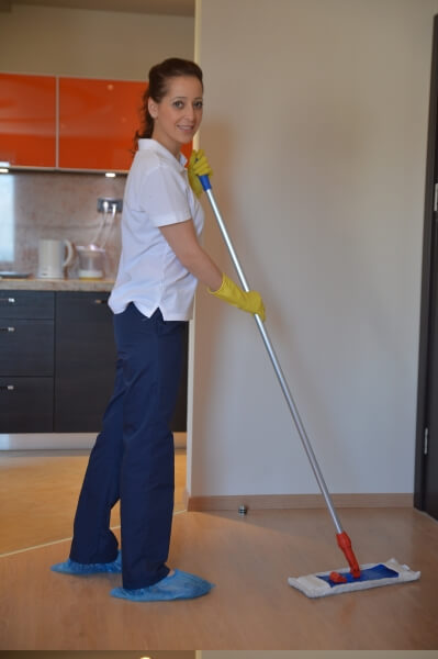 A home cleaner in London cleaning floor with a mop